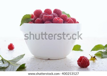 Fresh ripe raspberries in white bowl on rustic wooden table