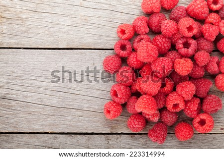 Fresh ripe raspberries on wooden table background with copy space - stock photo