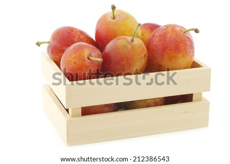 fresh ripe red and yellow plums in a wooden box on a white background