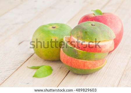Fresh ripe red apple and green orange on wooden table.