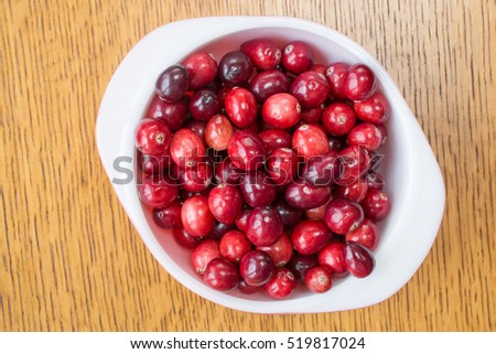 Fresh ripe red Cape Cod cranberries in a white bowl from above.