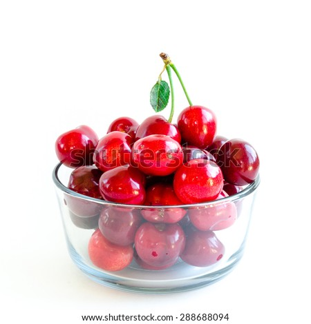 Fresh ripe red cherries with leaf on a glass bowl isolated on white background. They are fresh picked in Yakima Valley, a prime agricultural area of Washington State, US.