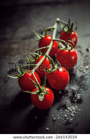 Fresh ripe red juicy cherry tomatoes in a bunch on the vine lying on a rustic kitchen counter with a scattering of salt and spices , shallow dof with copyspace - stock photo