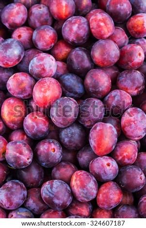Fresh ripe red plums as a background