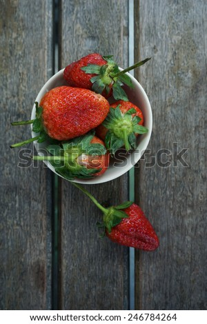 fresh ripe red strawberries in bowl on wooden textured table top view - stock photo