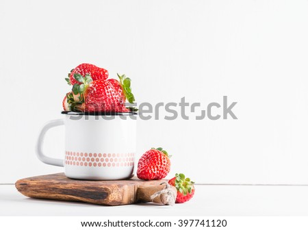 Fresh ripe red strawberries in country style enamel mug on rustic wooden board over white background, selective focus, copy space - stock photo