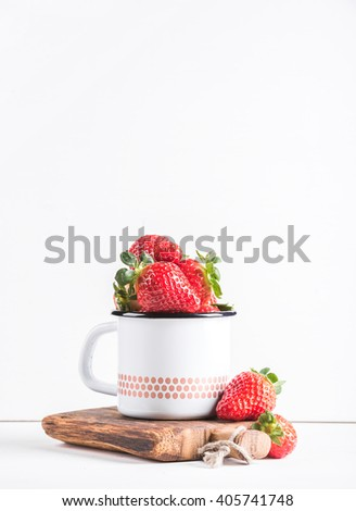 Fresh ripe red strawberries in country style enamel mug on rustic wooden board over white background, selective focus, vertical. Copy space - stock photo