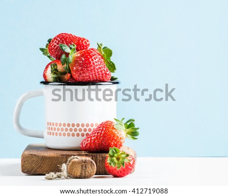 Fresh ripe red strawberries in country style enamel mug on rustic wooden board, pastel light blue background, selective focus, copy space - stock photo