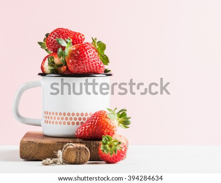 Fresh ripe red strawberries in country style enamel mug on rustic wooden board, pastel light pink background, selective focus, copy space - stock photo