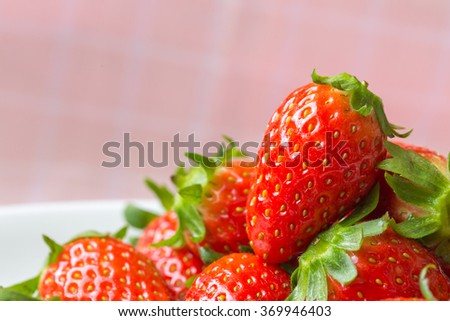 fresh ripe red strawberries on pink fabric
