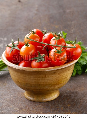 Fresh ripe red tomatoes in a wooden bowl - stock photo