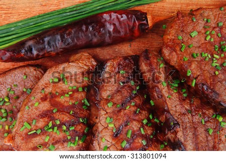 fresh ripe roasted beef meat on wooden plate with thyme and chives isolated on white background - stock photo