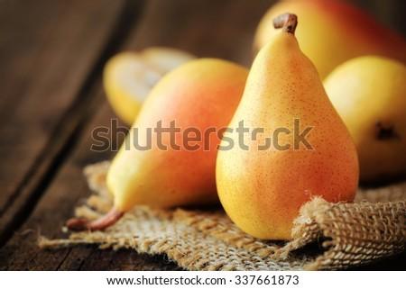 Fresh ripe Seckel pears on dark rustic wooden background
