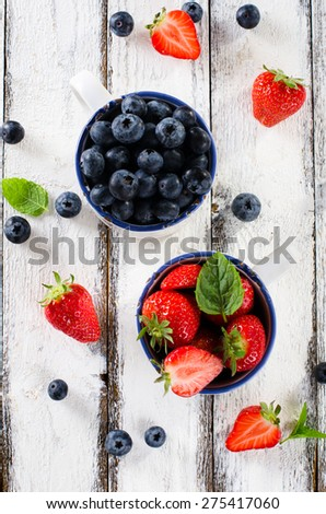 Fresh ripe strawberries and blueberries in white enamel mugs on  - stock photo