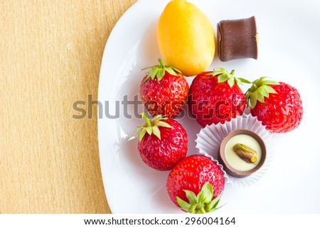 Fresh ripe strawberries, apricot and chocolate candy on white dish on table. Top view