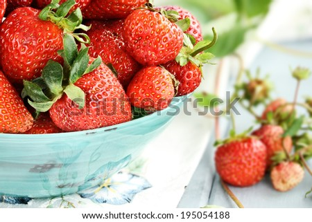 Fresh ripe strawberries in a beautiful blue bowl with selective focus and extreme shallow depth of field. - stock photo