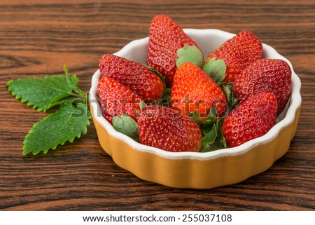 Fresh ripe strawberries in the bowl on wooden background - stock photo