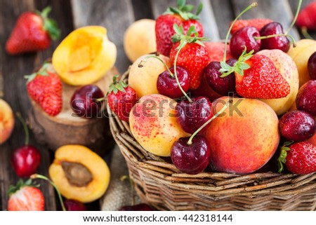Fresh ripe summer berries and fruits (peaches, apricots, cherry and strawberry) in wicker basket