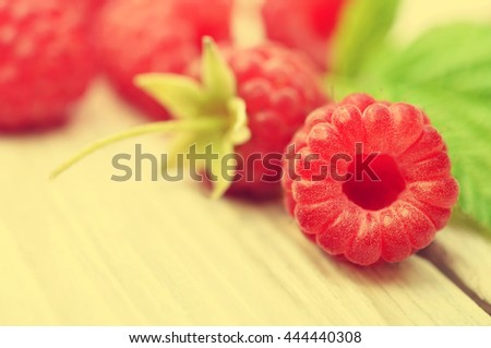 Fresh ripe sweet raspberries on wooden background, selective focus, shallow DOF, toned - stock photo