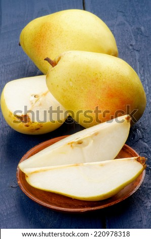 Fresh Ripe Sweet Yellow Pears Full Body, Half of and Slices isolated on Dark Blue Wooden background