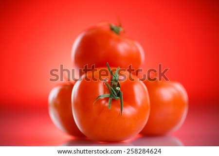 Fresh ripe tomatoes on a red background - stock photo