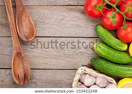 Fresh ripe vegetables and utensils on wooden table with copy space - stock photo