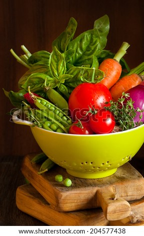 Fresh ripe vegetables in a green colander close-up.