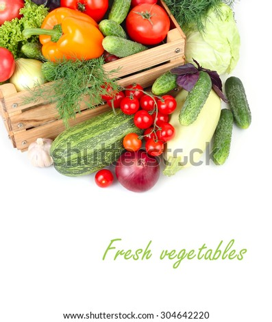 Fresh ripe vegetables in a wooden box on a white background with a place for the text. Top view. - stock photo