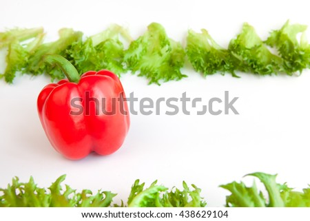 Fresh ripe vegetables - sweet  Red  Pepper and leaves of frillis. Bell peppers. - stock photo
