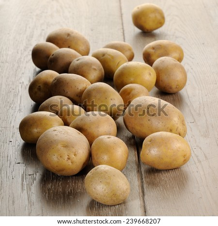 Fresh Ripe White Potatoes on wooden table