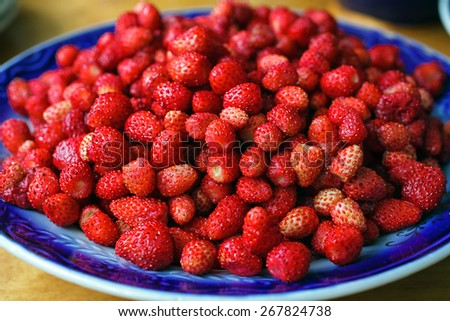 Fresh ripe wild strawberries in a bowl on wooden table - stock photo
