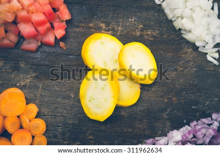 fresh ripe zucchini, carrots, tomatoes and onion chopped on a wooden board and shot from above. - stock photo