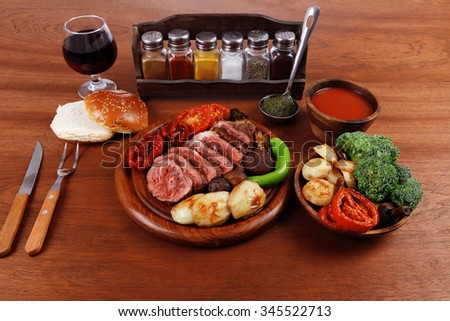 fresh roast bbq beef meat ribeye steak on wooden plate served with tomato juice wooden cup, boiled broccoli, baked tomatoes and potatoes, with white bun, and red wine glass light walnut wooden table
