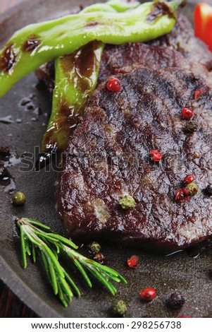 fresh roast beef fillet mignon on old retro style cast iron pan on retro wooden table as background with rosemary peppercorn and tomatoes - stock photo