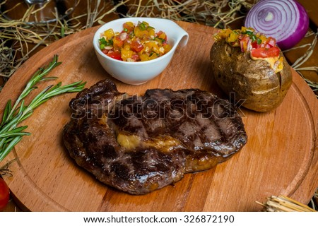 fresh roast beef meat ribeye steak on wooden plate served with baked potato and sauce