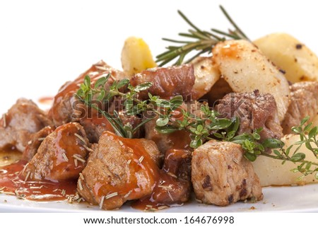 fresh roast pork in sauce with rosemary and potatoes