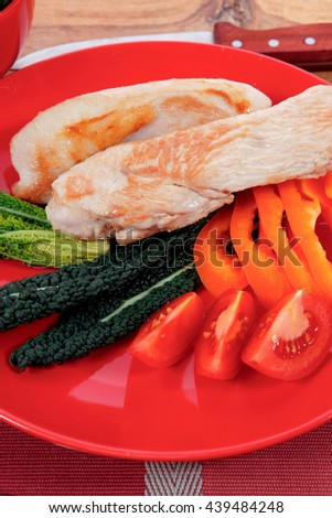 fresh roast turkey meat fillet steak on red plate with tomatoes pepper green kale and lettuce salad over wooden table - stock photo