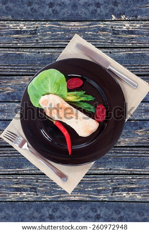 fresh roast turkey meat fillet steak served with vegetables on plate over blue wooden table - stock photo