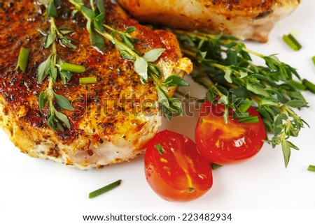 Fresh roasted pork meat steaks served with tomato and fresh herbs over white background - stock photo