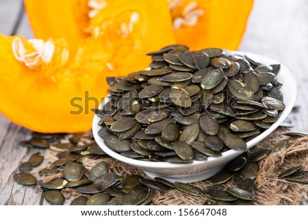 Fresh roasted Pumpkin Seeds on wooden background - stock photo