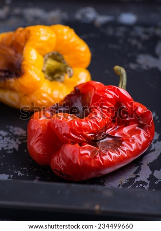 Fresh roasted red and yellow peppers over dark background, selective focus - stock photo