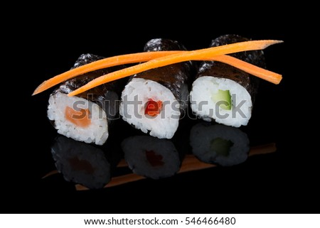 Fresh rolls with salmon, cucumber and pepper served with carrot slices, black background