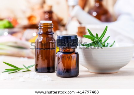 Fresh rosemary and essential oil with shallow depth of field setup on wooden background . - stock photo
