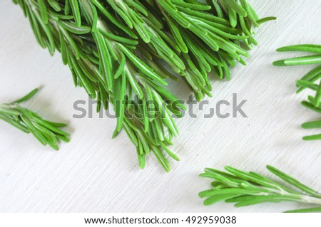 Fresh rosemary twigs on white wooden background