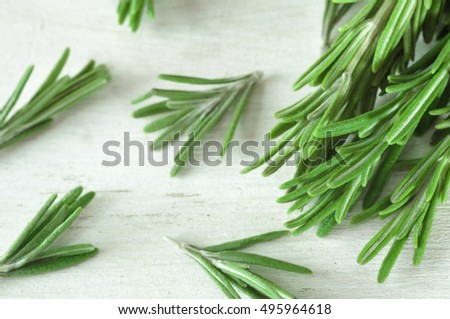 Fresh rosemary twigs on white wooden background. Heap of rosemary. Rosemary on the white table. Green rosemary. Rosemary close-up. Beam of rosemary. Food photo