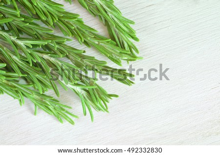Fresh rosemary twigs on white wooden background with copyspace