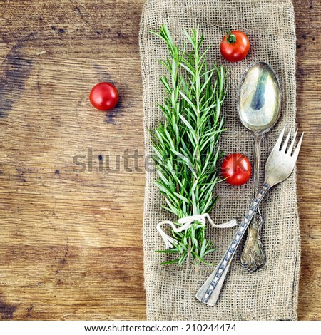 Fresh rosemary with red tomatoes on rustic wooden background - stock photo