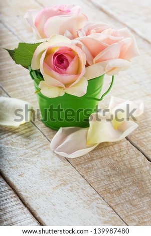 Fresh roses in bucket on wooden background. Selective focus. - stock photo