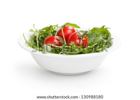 fresh rucola leaves in a bowl with tomatoes, isolated on white