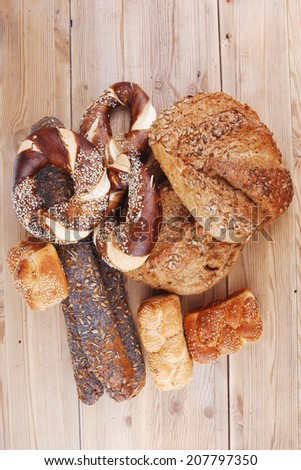 fresh rural homemade rye bread and baguette topped with sunflower seeds and sweet bagels on wooden tables - stock photo